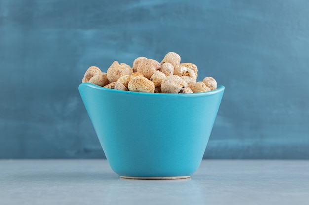 Eine blaue tiefe tasse voller köstlicher runder speisen.