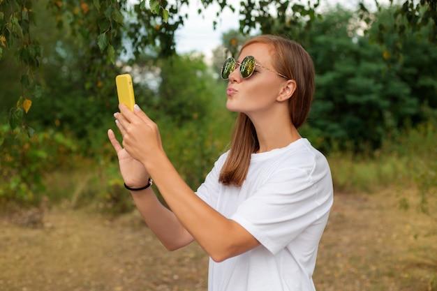 Eine bloggerin dreht ein video für ihre abonnenten in der natur