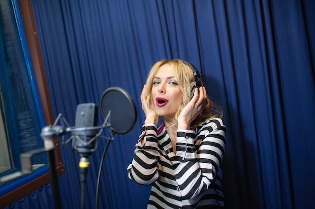 Eine blonde frau, die in ein mikrofon singt