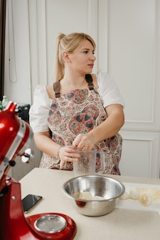 Eine blonde frau drückt zitronensaft mit der hand in den mixbecher in der küche.