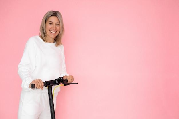 Eine blonde frau hält sich an einem elektroroller fest. porträt auf rosa hintergrund