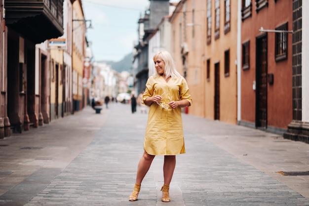 Eine blonde frau in einem gelben sommerkleid steht auf der straße der altstadt von la laguna auf der insel teneriffa. spanien, kanarische inseln.