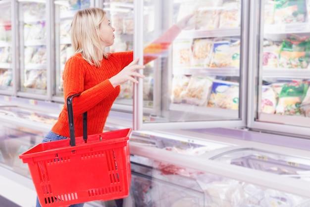 Eine blonde frau in einem orangefarbenen pullover wählt tiefkühlkost in einem supermarkt.