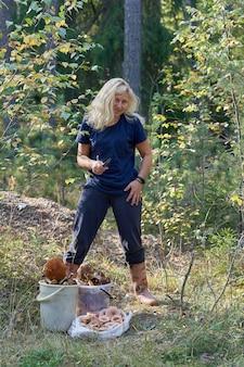 Eine blonde frau mit einem messer in der hand und lockerem haar steht im wald neben den gesammelten pilzen
