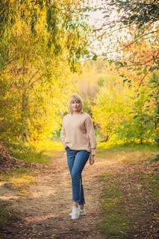 Eine blonde frau mit kurzem haarschnitt geht in einem strickpullover durch den wald. outdoor-wandern im herbstwald