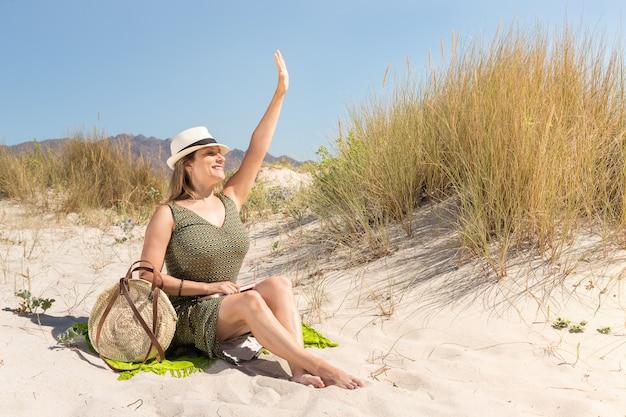 Eine blonde frau mittleren alters, die auf dem sand einer düne am strand sitzt und jemandem winkt