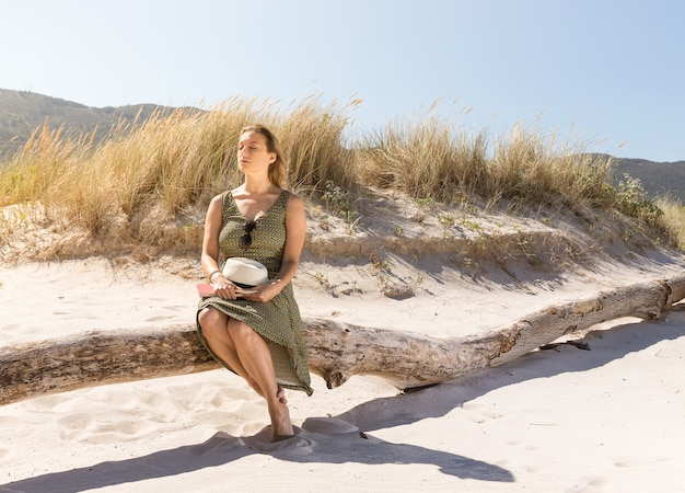 Eine blonde frau mittleren alters, die auf einem baumstamm am strand sitzt