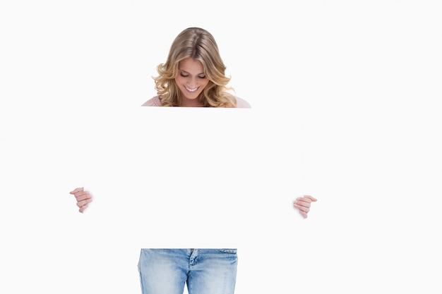 Eine blonde frau schaut auf ein weißes plakat, das sie hält