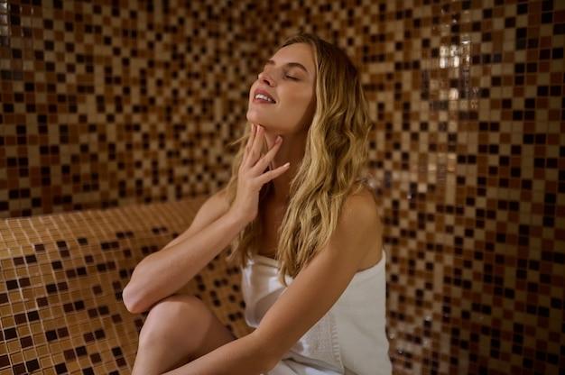 Eine blonde süße junge frau in einem hamam sieht entspannt aus