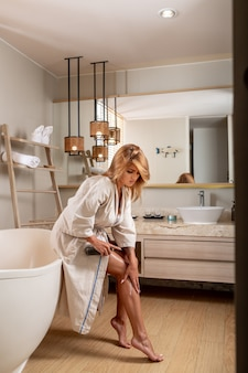 Eine blondine in einem weißen bademantel posiert gerastertes öl aus einer flasche auf ihrem bein, während sie auf der badewanne sitzt. körperpflege. körperöl. nahansicht. körperpflegekosmetik. vertikales foto.