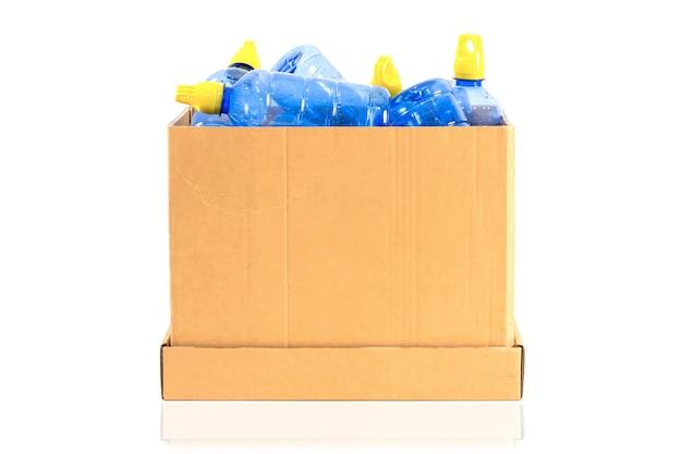 Eine box mit einer plastikflasche, die auf einem weißen hintergrund recycelt werden soll