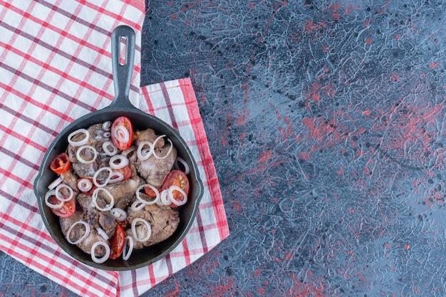 Eine bratpfanne mit leckerem fleisch mit pfeffer und zwiebeln.