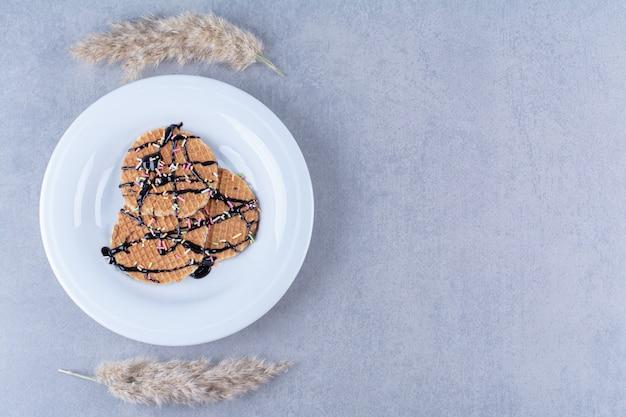 Eine bratpfanne mit runder rötlicher waffel mit streuseln und sahne