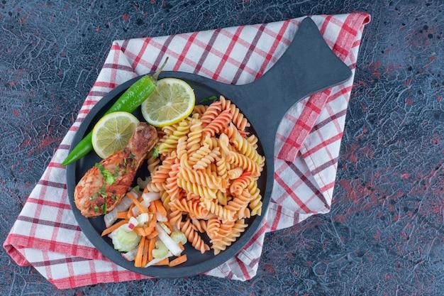 Eine bratpfanne mit spiralförmigen makkaroni und hühnerbeinfleisch.