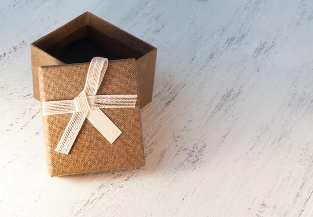 Eine braune geschenkbox und ein beige band mit einem tag auf einem hellen hintergrund. ein weihnachtsgeschenk. tonen und unschärfe.