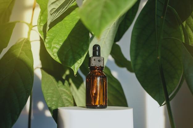 Eine braune glasflasche mit ätherischem serumöl oder einem anderen kosmetischen produkt zwischen großen avocadoblättern