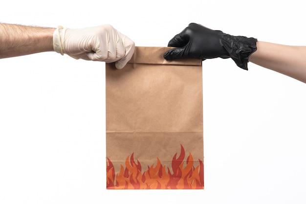 Eine braune lebensmittelverpackung in vorderansicht, die sowohl in handschuhen als auch von männern geliefert wird