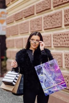 Eine braunhaarige frau, die schwarze kleidung trägt, hält bunte, gemusterte einkaufstaschen während eines erfolgreichen einkaufsbummels. wenn sie nach draußen geht, genießt sie die wärme eines tages