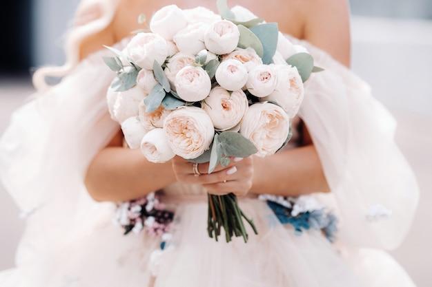 Eine braut in einem hochzeitskleid hält einen strauß rosen in den händen vor sich.