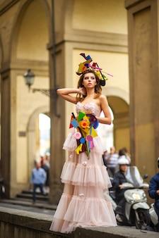 Eine braut in einem rosa hochzeitskleid mit einem ungewöhnlichen blumenstrauß und einer dekoration in gorova in florenz, italien. Premium Fotos