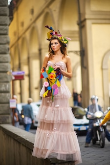 Eine braut in einem rosa hochzeitskleid mit einem ungewöhnlichen blumenstrauß und einer dekoration in gorova in florenz, italien.