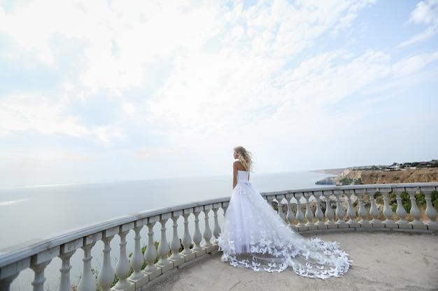 Eine braut in einem schönen weißen hochzeitskleid steht an einem sonnigen sommertag auf einem balkon auf einem berggipfel