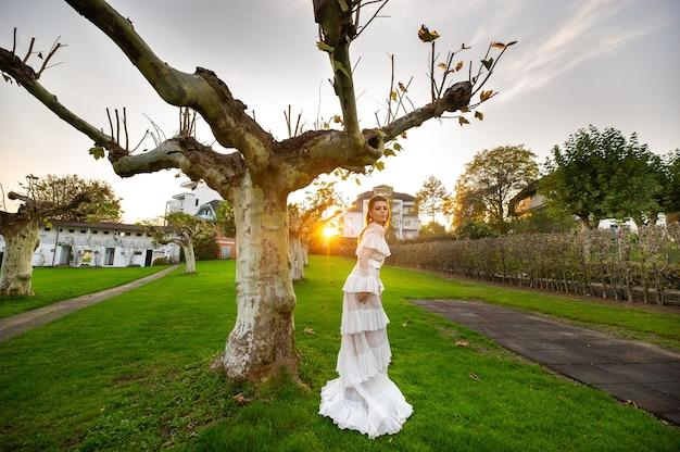 Eine braut in einem weißen hochzeitskleid in einem park in einer österreichischen stadt mit großen bäumen bei sonnenuntergang.