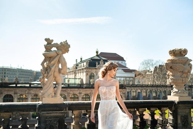 Eine braut in einem weißen kleid auf einem hochzeitsspaziergang im berühmten barocken zwinger in dresden, sachsen, deutschland
