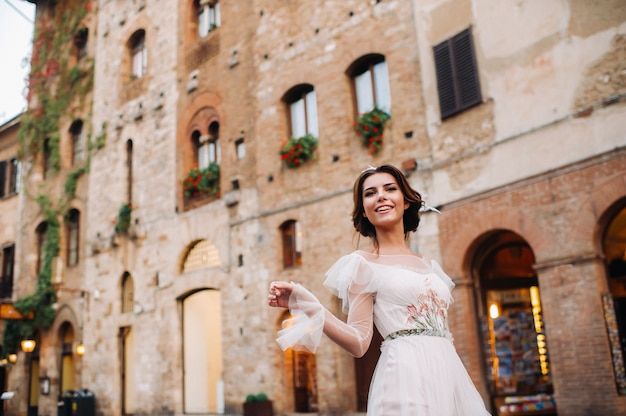 Eine braut in einem weißen kleid in der altstadt von san gimignano. ein mädchen geht durch die stadt in italien. toskana.