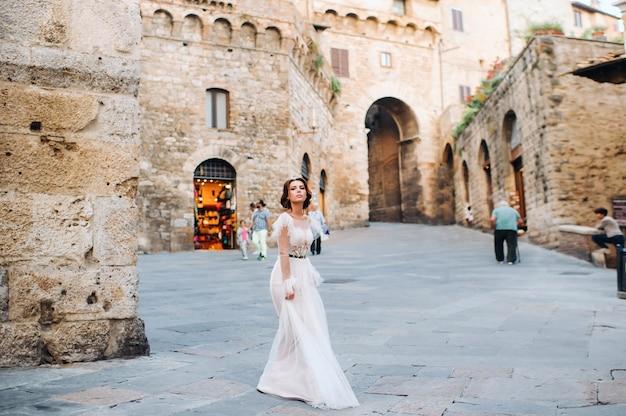 Eine braut in einem weißen kleid in der altstadt von san gimignano.