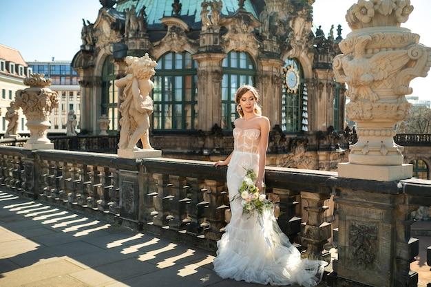 Eine braut in einem weißen kleid mit einem blumenstrauß auf einem hochzeitsspaziergang im berühmten barocken zwinger in dresden, sachsen, deutschland.
