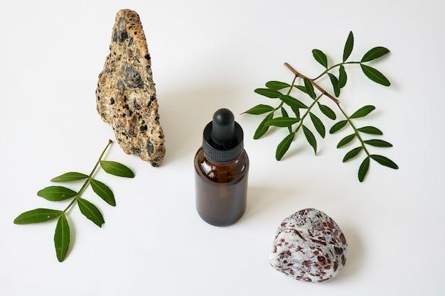 Eine brawn-flasche mit einer mit essenzöl oder parfüm gefüllten pipette vor dem hintergrund von steinen