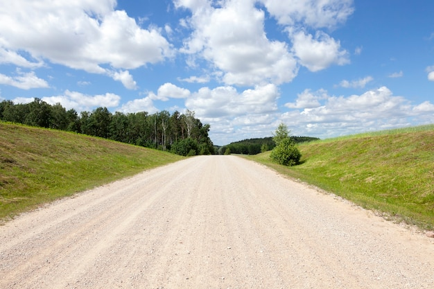 Eine breite landstraße gegen einen blauen himmel mit wolken. an den straßenrändern wachsen mais und wald