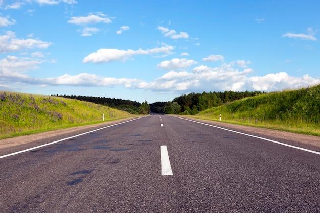 Eine breite straße aus asphalt, gebaut durch einen wald mit verschiedenen bäumen, sonniges wetter mit blauem himmel