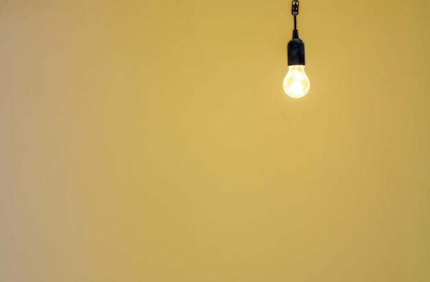 Eine brennende glühbirne auf dem hintergrund einer gelben wand