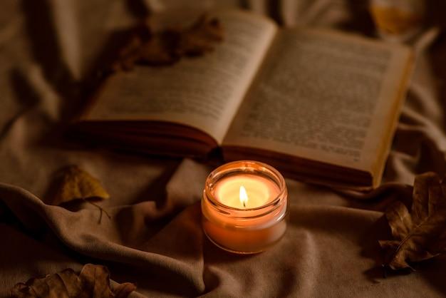 Eine brennende kerze auf einem holztisch vor einem buch in einem halbmast. lernen. die bibel studieren