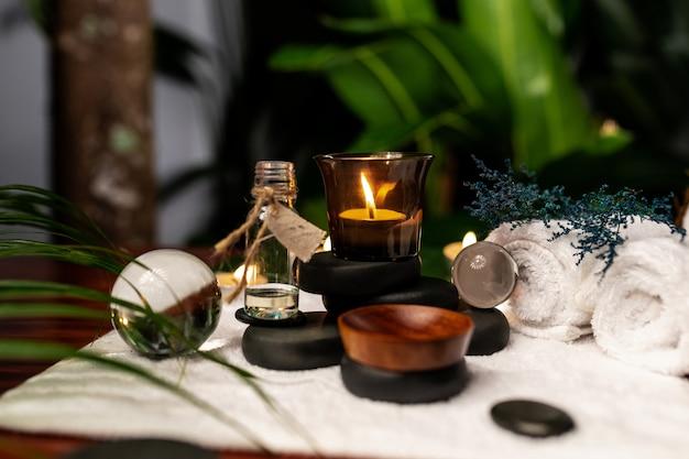 Eine brennende kerze und ein glas aromaöle stehen auf steinen zur steintherapie