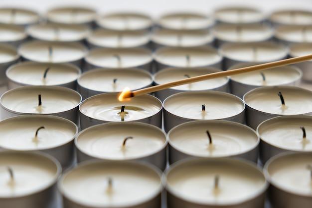 Eine brennende kerze und viele erloschene kerzen