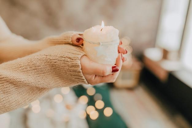 Eine brennende weiße kerze in den händen einer frau das konzept einer urlaubskomfortwärme