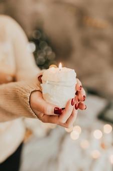 Eine brennende weiße kerze in den händen einer frau. das konzept eines urlaubs, komfort, wärme. vertikales foto