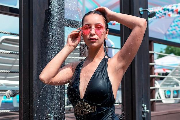 Eine brünette frau duscht im freien, eine dusche in der nähe des pools