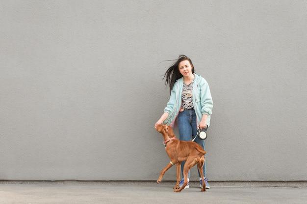 Eine brünette frau in freizeitkleidung mit einem hund haben