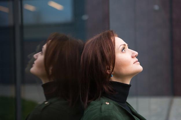 Eine brünette frau mit bob-haarschnitt steht mit dem rücken zur spiegelwand, wird reflektiert und sieht traurig aus. das thema einsamkeit