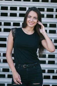 Eine brünette frau mit langen haaren, die ein leeres schwarzes t-shirt trägt