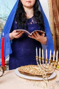 Eine brünette jüdin mit einem blauen umhang am pessach-seder-tisch liest die pessach-haggada. vertikales foto