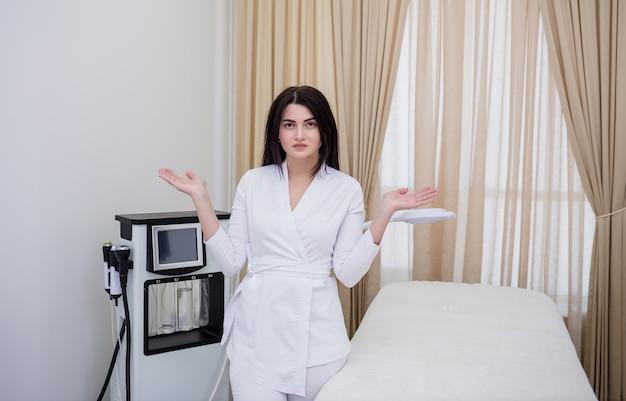 Eine brünette kosmetikerin steht in weißer uniform im büro