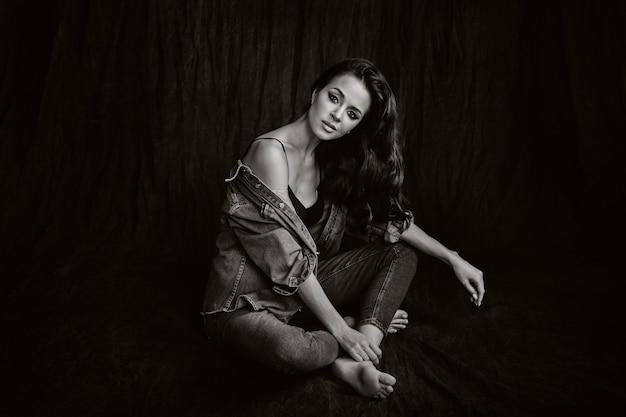 Eine brünette mit langen haaren posiert im studio auf einem schwarzen hintergrund auf dem boden sitzend. schwarz-weiß-foto