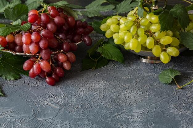 Eine bürste mit roten trauben in einem silbernen teller und eine bürste mit hellen trauben, eine rebe
