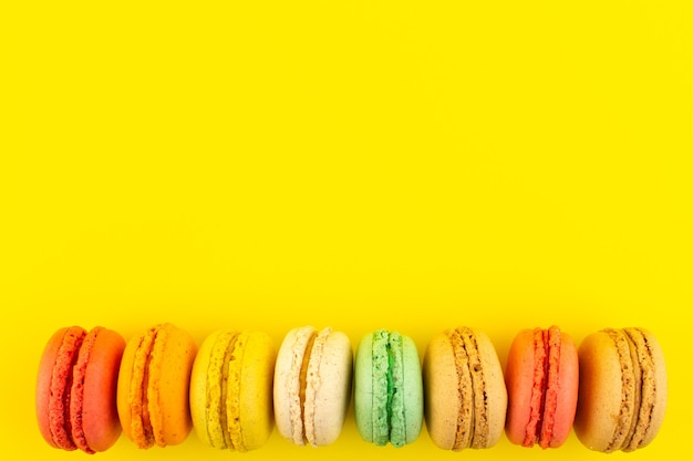 Eine bunte französische macarons der draufsicht, die auf dem gelben schreibtischzuckerkuchenkeks süß schmeckt