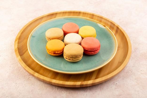 Eine bunte französische macarons der draufsicht, die innerhalb des runden tellers auf dem rosa schreibtischkekskuchenzuckersüß köstlich ist
